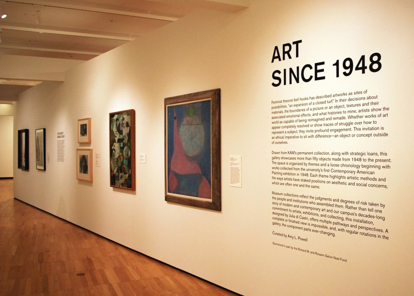 "Image: Installation of ""Art Since 1948"" at Krannert Art Museum. The title wall of the exhibition features text on the right side of the image, with six wall-hung, two dimensional works of art hung to the left of the text. The text is black; the wall is white. Photo by Jessica Hammie."