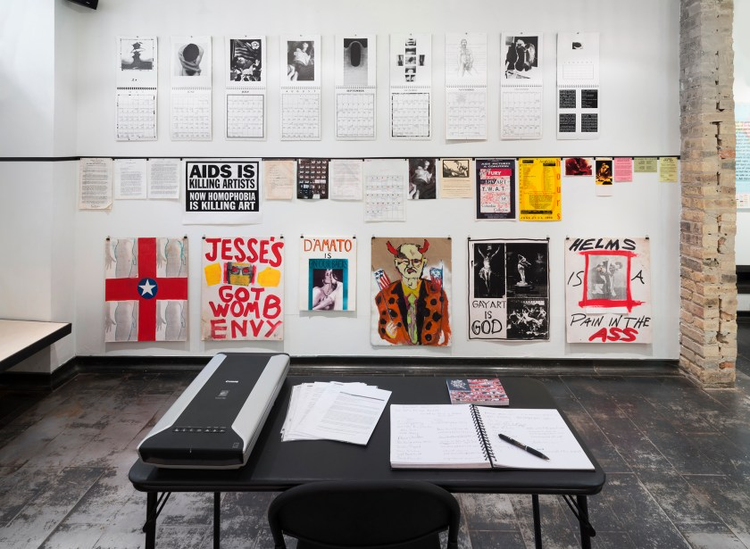 "Image: Installation shot of Iceberg Projects exhibition ""Militant Eroticism: The ART+ Positive Archives,"" May 30 – June 27, 2015. This image is of a room in Iceberg Projects. Numerous calendars hang on the wall directly in from of the viewer. In the center of the room, there is a folding table with an open notebook, a pen, some papers, and an electronic device. Image courtesy of Iceberg Projects."