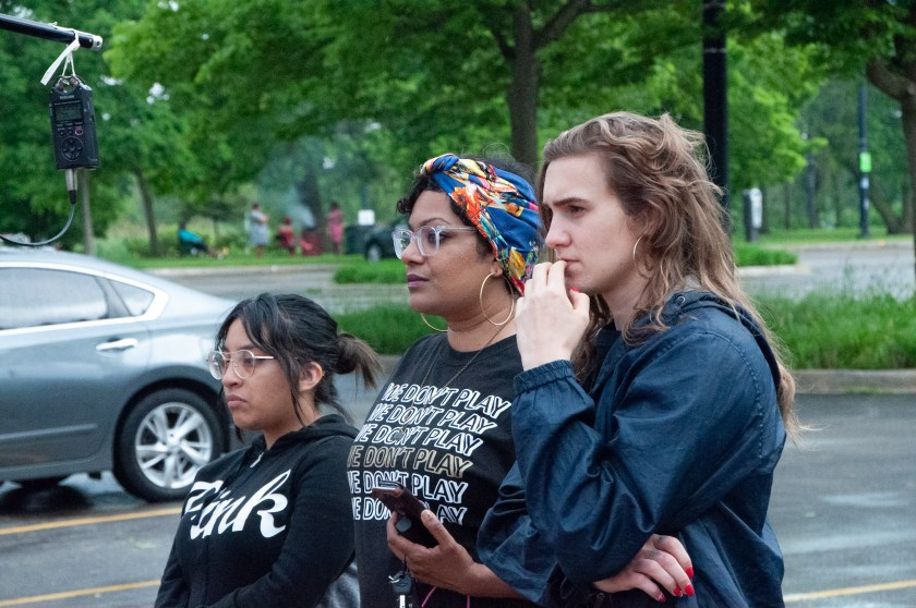 "Image: Tanuja Devi Jagernauth (center) stands in a parking lot with Katrina Dion (right) and an audience member, intently watching an outdoor pop-up performance as part of ""50 in 50"" — Free Street Theater's 50th anniversary celebration involving 50 performances in all of Chicago's 50 wards in one day. They are positioned in near-profile, looking off-camera. Jagernauth wears a black t-shirt reading ""WE DON'T PLAY,"" glasses, and hoop earrings. The others wear dark-colored zip-up hoodies. A sound recorder hangs from a pole in the top left-hand corner of the frame, and the space farther behind the onlookers is lush and green. Courtesy of Free Street Theater. Photo by Lena Jackson."