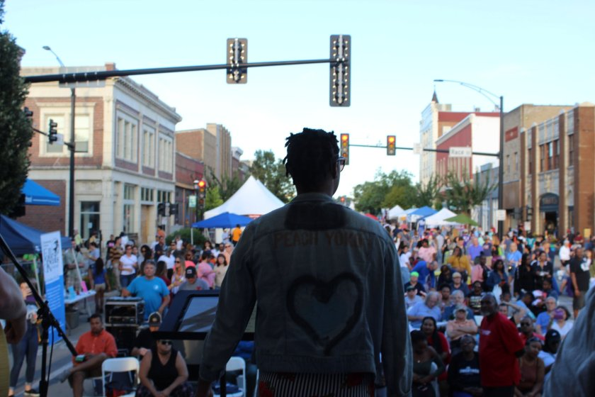 Image: New Souls performing on a stage at Urbana's Downtown Get Down in August 2019. The photograph is taken from behind the band, looking out toward the crowd. A Black woman is the lead singer and standing in the middle of the stage. She is wearing a jean jacket with a heart on the back. A large crowd is in front of the stage, which is set up in the middle of a street. Buildings line each side of the street, and tops of tents are visible in the distance. Photo courtesy of Urbana Arts & Culture Program.