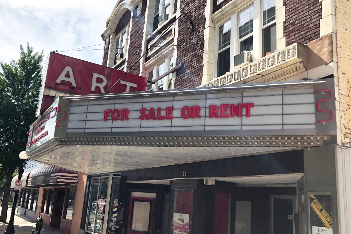 """Featured Image: The marquee of The Art Theater in Champaign, Illinois reads """"For Sale or Rent."""" The Art Theater's sign is red and retro. The brick building is located on a downtown street, with residential apartments above the theater. Photo by Jessica Hammie."""
