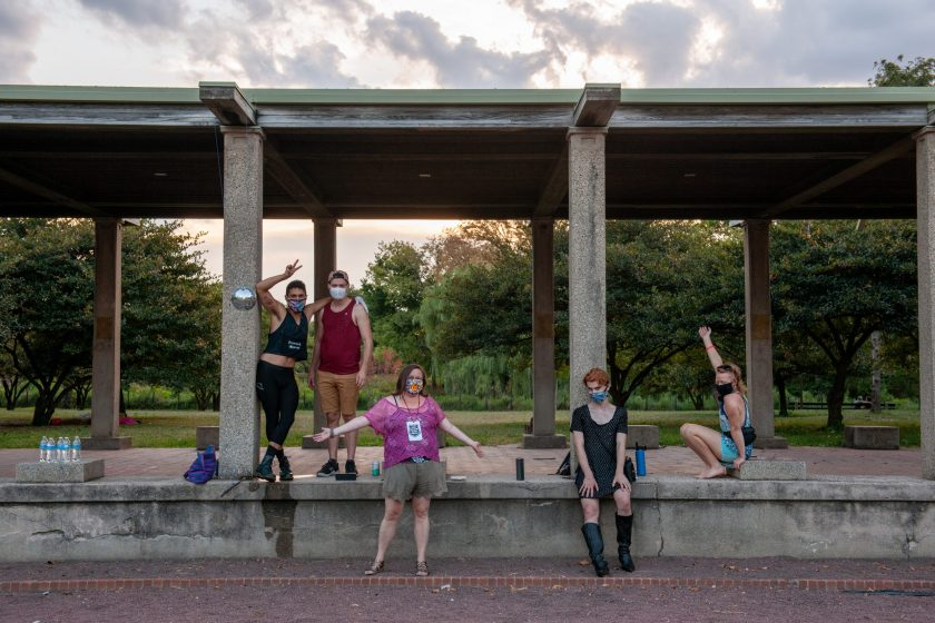 Image: A group of poets in various poses under and on a structure in Humboldt Park.