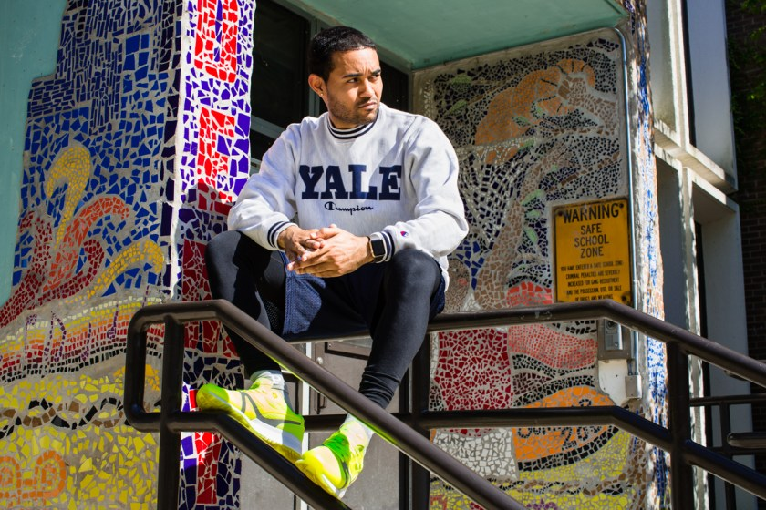 Image: Kristoffer McAfee is sitting on a metal railing in front of a doorway covered in colorful mosaic tile. He is wearing a Yale sweatshirt and look to the right with his hands together.  Photo by Kristie Kahns.