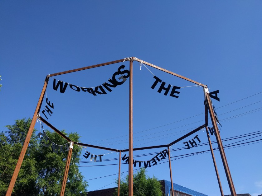 """Image: """"Untitled Politics"""" by Uniymeabasi Udoh, installed on July 13, 2020 at El Paseo Community Garden on Cullerton St and Csangamon St. in East Pilsen. Letter garlands are installed across the tops of an octagon metal frame. The letters in the foreground spell """"WORKINGS"""" and """"THE"""". Photo by Cecilia Resende Santos."""