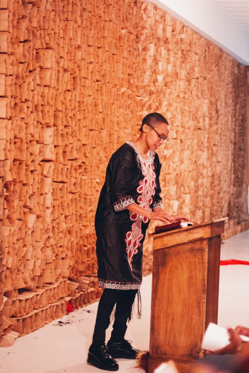 A photo of Tiff Beatty, the unofficial pastor of The People's Church, standing at a podium with her hands on a book, looking down and speaking to the audience. Photo by Candice Majors.