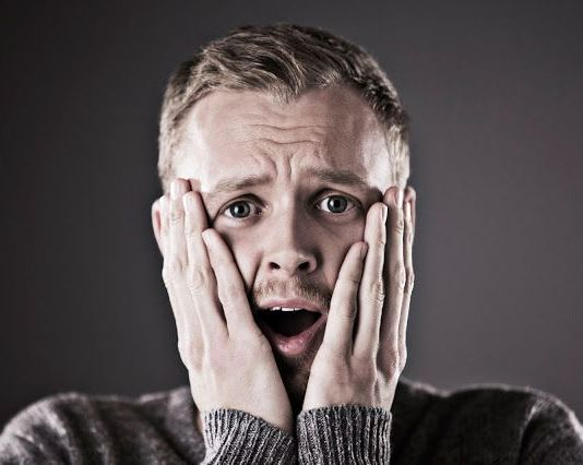 elleri yüzünde bir adam, ağzı açık ve korkmuş
