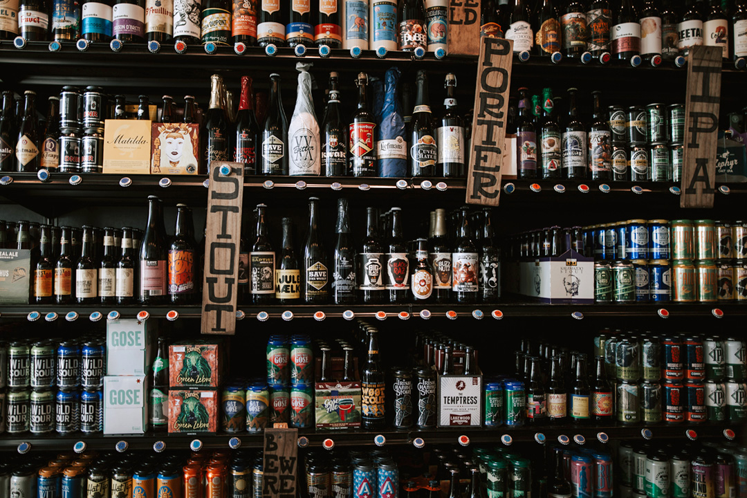 A stocked beer shelf featuring a bunch of different styles