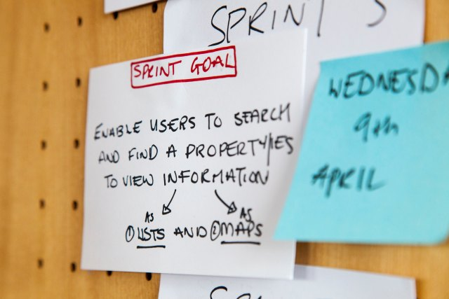 Sprint Goal in red letters on white post it note, on a wooden wall with other post it notes around it