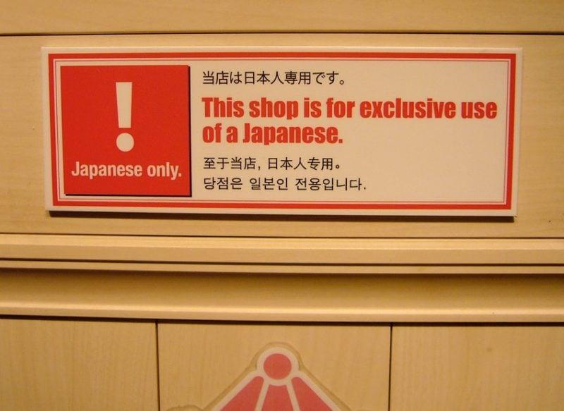 Placa de um estabelecimento escrita em japonês, inglês, chinês e coreano. A placa avisa que a loja é uso de exclusivo de japoneses.