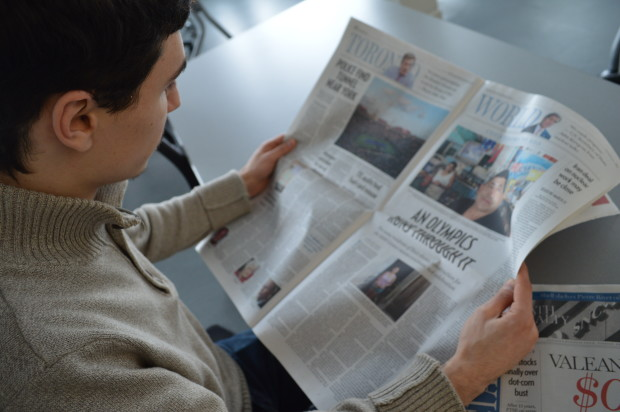 A picture of a guy in a sweater reading the newspaper.