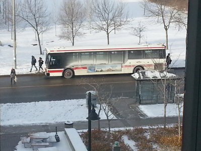 A TTC bus stopping on the road on a winter day.