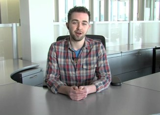 A guy sitting at a desk with his hands folded talking to the camera.