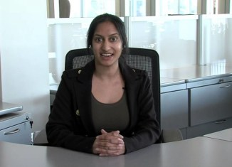 A picture of a girl sitting at a desk with her hands folded.