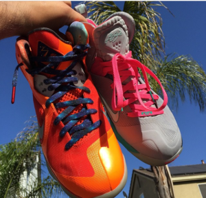 A hand holding a pair of mismatched Nike shoes. The left shoe is orange with blue laces and the right side is grey with pink laces.