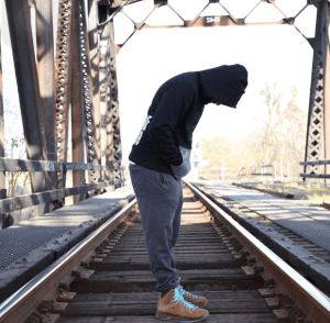 A man wearing a hooded sweat shirt standing on a train track with his hands in his pockets looking down.