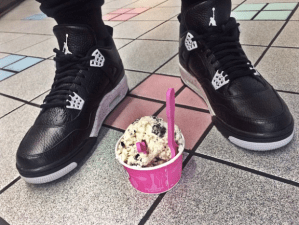 A scoop of Baskins Robbins cookies and cream ice cream with two spoons in it sitting on the ground in between a pair of black and white shoes on someones feet.
