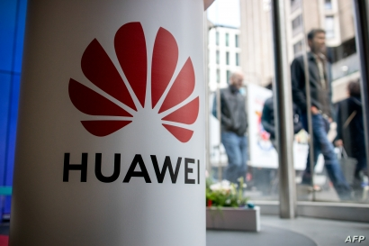 A pedestrian walks past a Huawei product stand at an EE telecommunications shop in London, April 29, 2019
