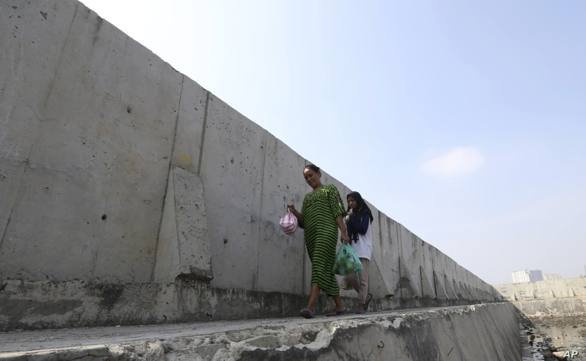 Women walk near a giant sea wall used to prevent sea water from flowing into Jakarta, Indonesia, July 27, 2019. Indonesia's president wants to see the speedy construction of the giant sea wall to save the low-lying capital of Jakarta from sinking under the sea.
