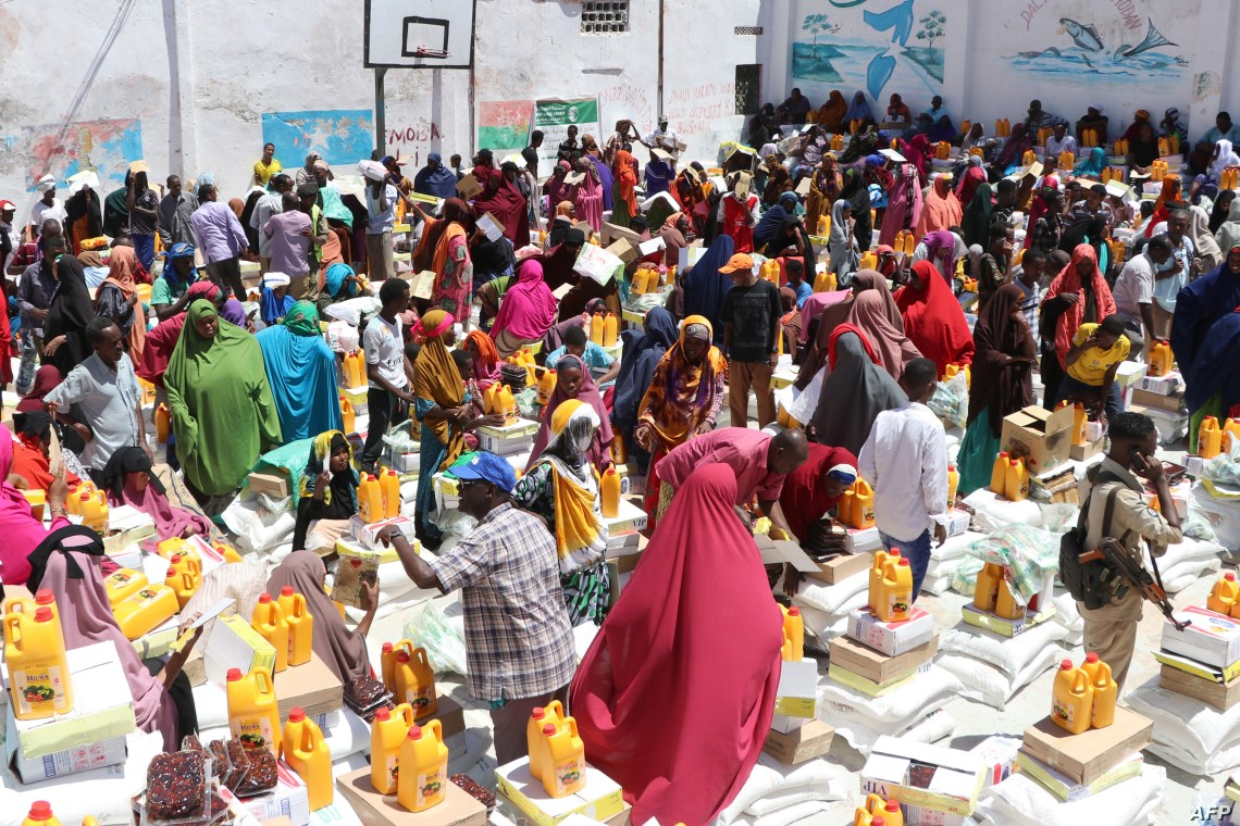 FILE - Internally displaced people gather to collect food rations being distributed to the families in the Shingani District of the Somali capital, Mogadishu, May 15, 2019.