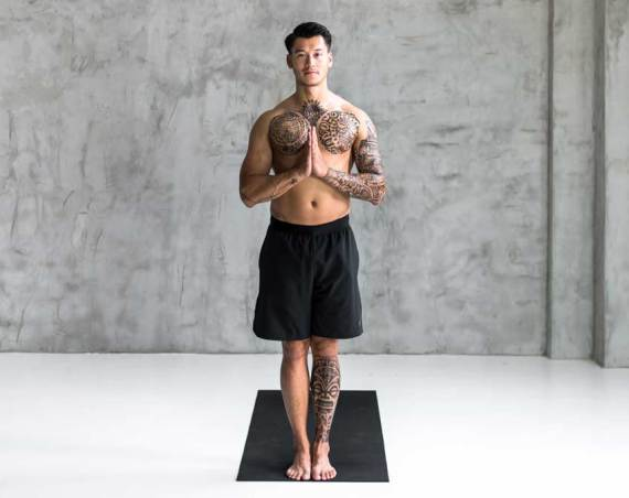 man standing with hands in prayer position