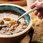 A close-up of a bowl of mushroom barley soup, with a spoon and, a piece of bread.