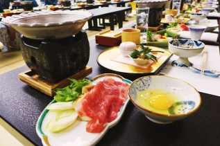 Sukiyaki, prepared and served in a shallow iron hot pot resting on top of its etched stand. Foreground: slices of beef, leeks, and scallions moments before simmering in a mixture of soy sauce, sugar, and miriin. The egg was beaten and used as a dipping sauce for the cooked meat and assorted vegetables.