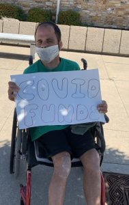 Tyson in wheelchair holding sign that reads Covid Funds for Medicaid Expansion protest