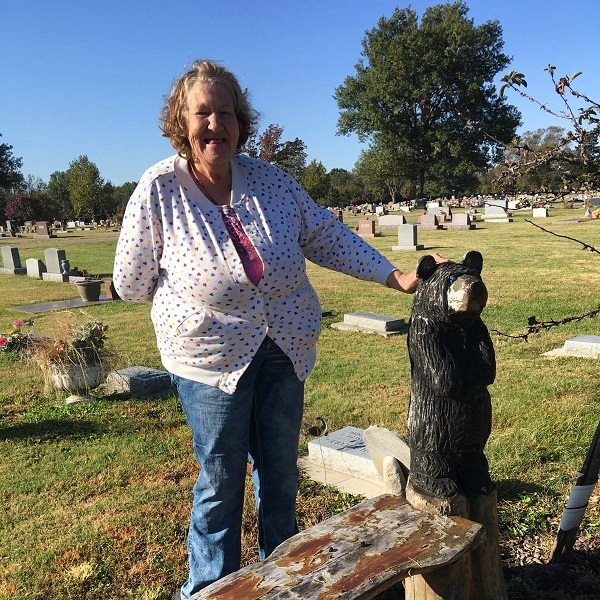 Lucy standing next to bear statue at gravesite