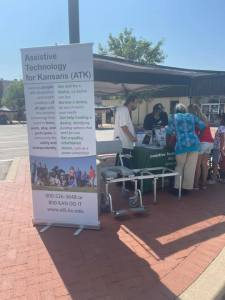 People gathering under a tent with a large board reading Asssistive Technology for Kansas ATK