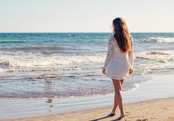 woman walks on the beach towards the ocean