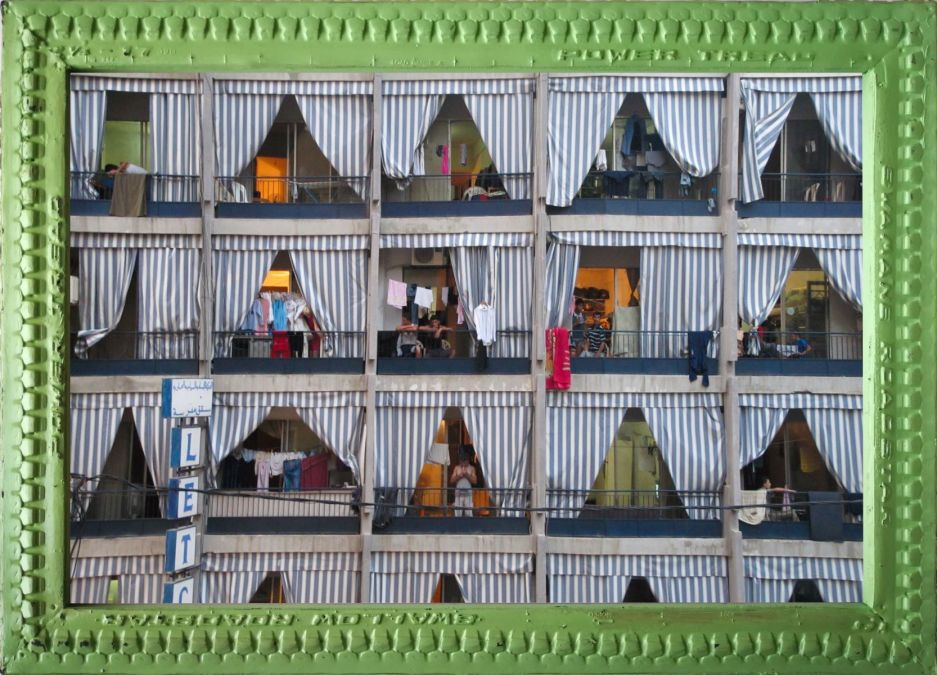 An image of the artwork Beirut Windows. A photograph showing a grid of balcony windows seen from outside with matching striped curtains. A few people can be seen, laundry hangs on lines and railings. The photograph is in a pale green patterned wooden frame.