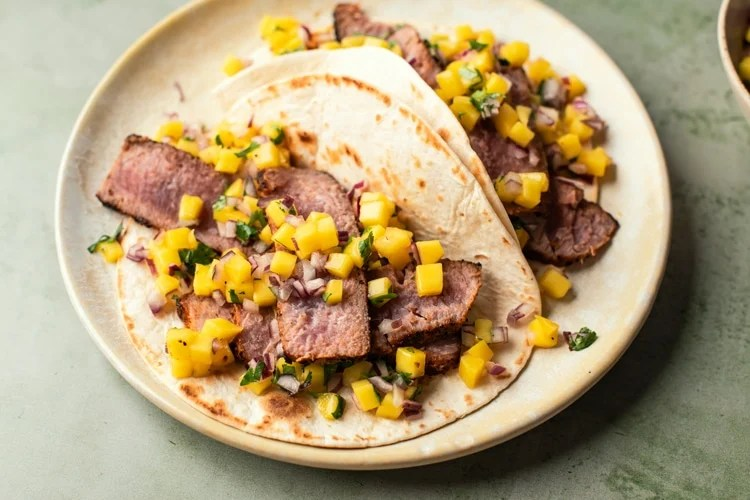These grilled tuna tacos with fresh mango and pineapple coleslaw are the perfect recipe for a summer dinner!