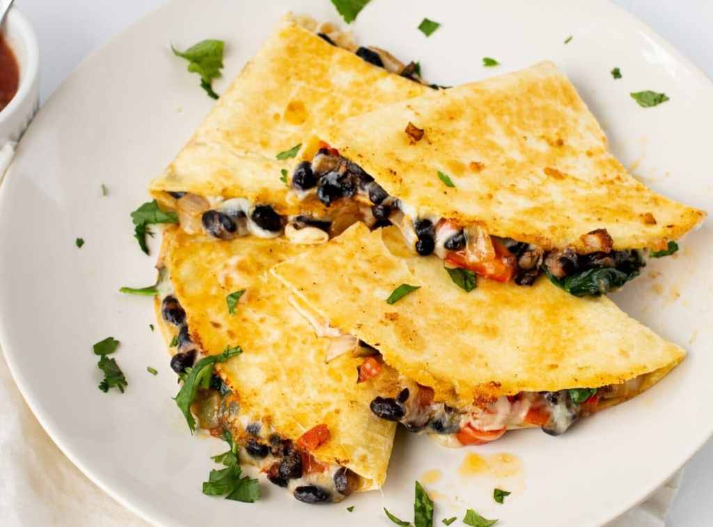 Our thin black bean quesadillas are full of cheesy goodness and fresh vegetables!
