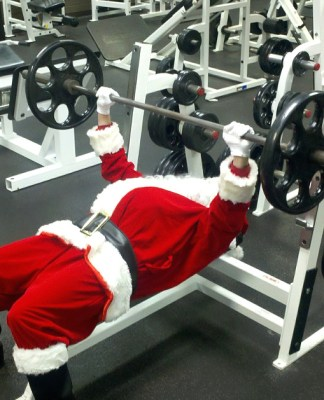 Father Christmas in gym lifting weights