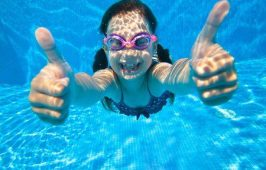 45903149 - little girl dives into the water and shows the gesture ok
