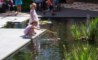 Fashion Island at Newport Beach. Little girls playing by the koi pond. Added some gaussian blur to the background.