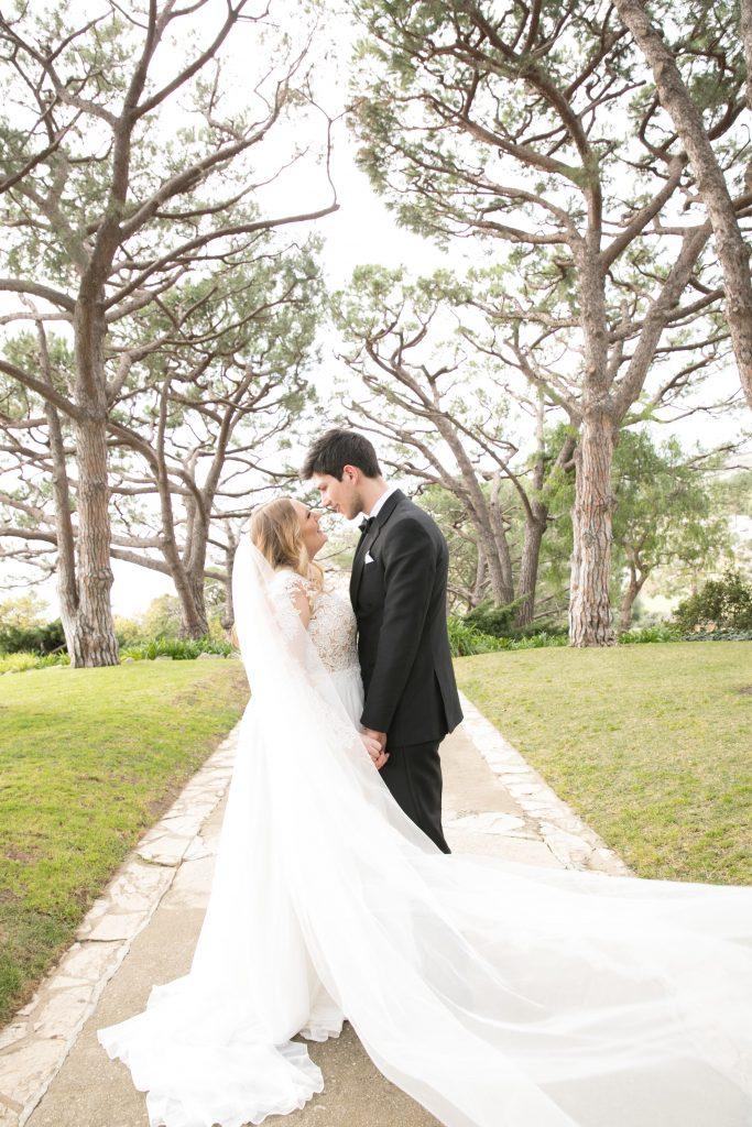 bride with long veil almost kisses groom in Palos Verdes