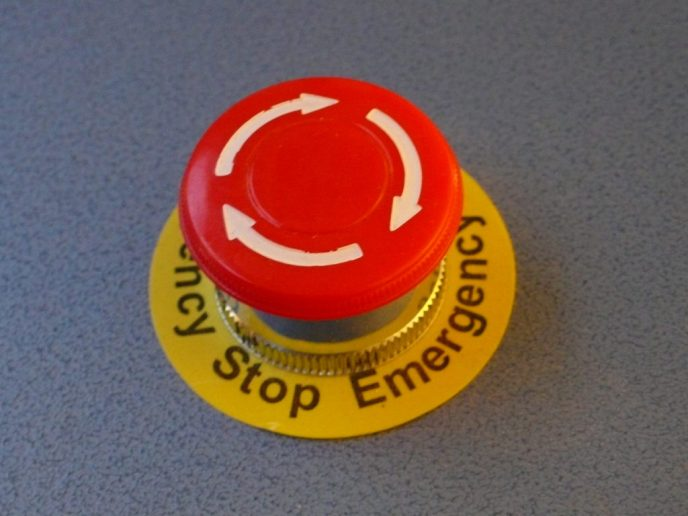 A red emergency stop button that would be present throughout a factory for use in an emergency to stop the factory.