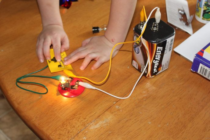 A child pushing down on a paperclip to turn on a light in a simple electrical experiment.