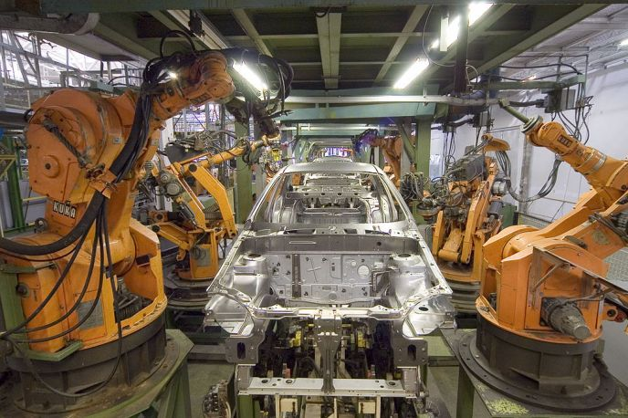 An automated assembly line where orange Kuka robots are performing a joining operation on an automotive body as it proceeds down the assembly line.