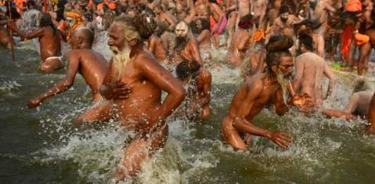 """Millions of Hindu pilgrims took the plunge into sacred rivers at the world's largest religious gathering Monday, led by ash-smeared holy men and accompanied by religious chanting. On the most auspicious day of the months-long Kumbh Mela festival, devotees rose at dawn in the northern city of Allahabad to immerse themselves at the confluence of three rivers -- the Ganges, the Yamuna, and the mythical Saraswati. Thousands of Naga Sadhus, a devout, fierce and famously nude sect of followers of the Hindu god Shiv, and other holy men clad in saffron robes, led the mass bathing in the chilly waters, some brandishing swords and tridents. Hindus believe that bathing in the sacred rivers cleanses them of sin and Monday's Mauni Amavasya Snan -- the """"no moon day"""" -- is considered the holiest of the gigantic 48-day festival that runs until March 4. More than 30,000 police were on duty to manage the huge crowds and prevent the deadly stampedes that have marred previous gatherings. Authorities have spent about $40 million on an operation to block drains and make sure others undergo special cleansing so that waste water pouring into the rivers does not threaten the pilgrims. AFP / SANJAY KANOJIA Pilgrims have been streaming into a temporary tent city three times the size of Manhattan island to participate in the festival's high point Special skimmer boats collected waste from the surface of the rivers and more than 40,000 temporary toilets have been installed. Pilgrims have been streaming into a temporary tent city -- three times the size of Manhattan island -- in buses, trains and cars to participate in the festival's high point. The confluence of the three rivers is considered especially holy and Hindus believe bathing there during the Kumbh helps cleanse sins and bring salvation. Nearly 12 million people attended the inaugural bathing ritual on January 15 and about 120 million are expected during the whole festival. Devotees meditate on the banks of the rivers after the dip and"""