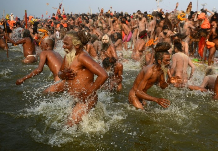 Millions of Hindu pilgrims took the plunge into sacred rivers at the world's largest religious gathering Monday, led by ash-smeared holy men and accompanied by religious chanting. On the most auspicious day of the months-long Kumbh Mela festival, devotees rose at dawn in the northern city of Allahabad to immerse themselves at the confluence of three rivers -- the Ganges, the Yamuna, and the mythical Saraswati. Thousands of Naga Sadhus, a devout, fierce and famously nude sect of followers of the Hindu god Shiv, and other holy men clad in saffron robes, led the mass bathing in the chilly waters, some brandishing swords and tridents. Hindus believe that bathing in the sacred rivers cleanses them of sin and Monday's Mauni Amavasya Snan -- the