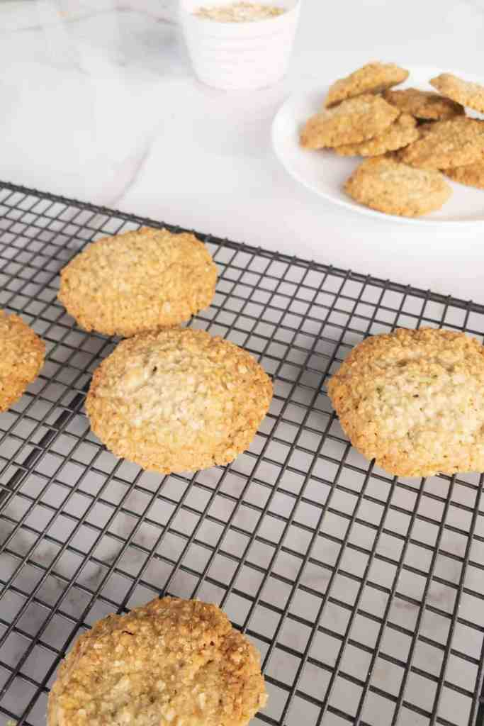 coconut and oatmeal cookies on a rack beside a plate of cookies