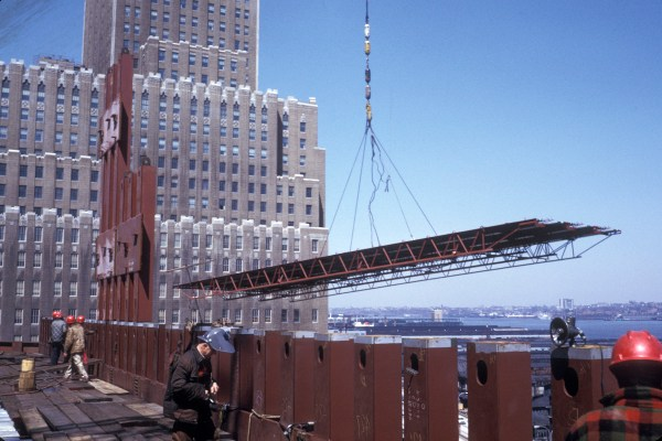 Tower crane lifting a a prefabricated floor panel measuring 20 by 60 feet.