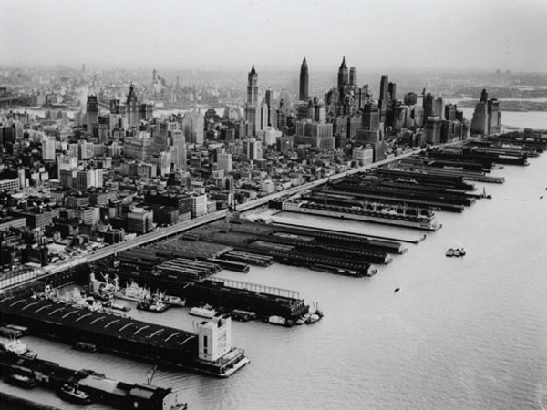 Aerial view of West Street and Hudson Yards in the foreground and the skyline of Lower Manhattan in the background