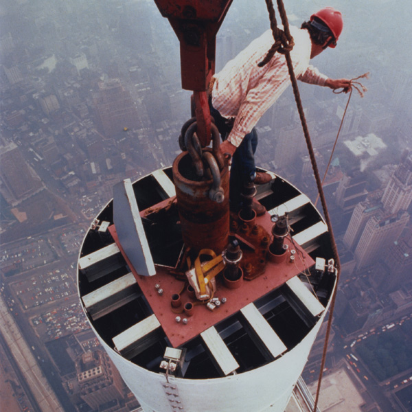 Photograph of a worker installing the antenna of the World Trade Center, looking down street level. Photograph by Peter B. Kaplan