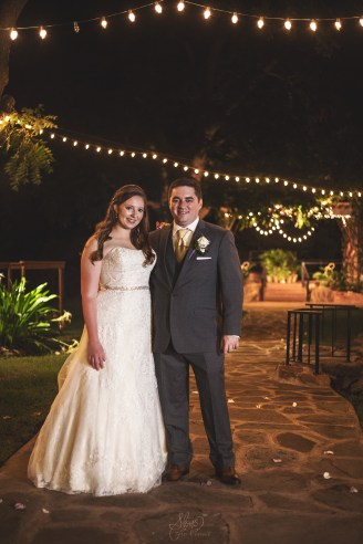 Wedding couple underneath the lights at night at the Bernhardt winery in plantersville texas.