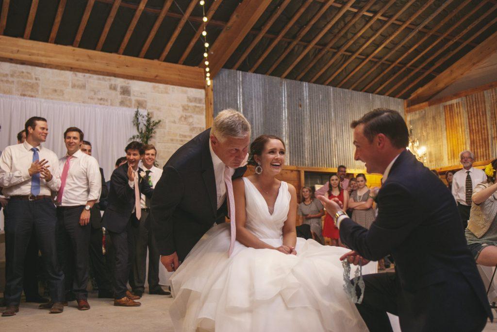 Dad of the bride teasing groom during garter toss