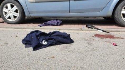 Samochód, a na jezdni leżą różne przedmioty, w tym fragment odzieży z napisem Policja.