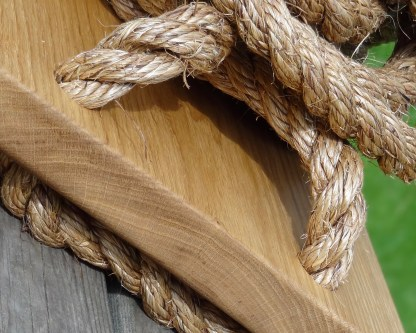 side view of a solid oak traditional swing where the manilla rope is threaded through the swing base then spliced so far up the length